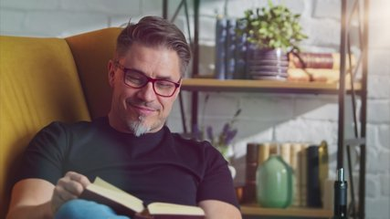 Older man in glasses resting at home sitting in armchair reading book. Cosy mood at home.
