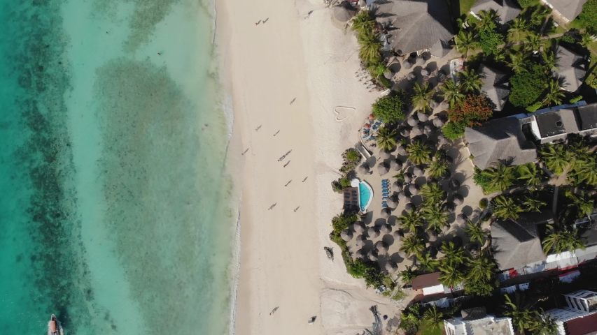 Aerial view of Thatched roof of beach umbrellas of luxury ocean view resort at the beautiful white sand ocean coast in Nungwi at Zanzibar island, Tanzania | Shutterstock HD Video #1047926611