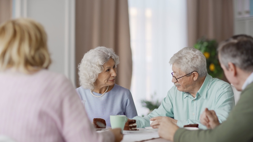 Group of four senior friends sitting at dining table at home and enjoying talk over dessert. Smiling elderly woman with curly grey hair speaking