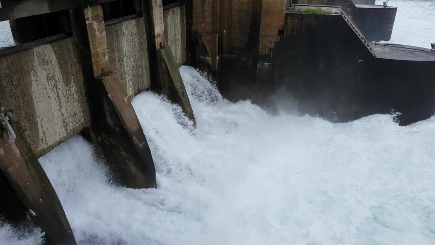 Spring flood water flowing on hydroelectric power station dam. | Shutterstock HD Video #1047933163