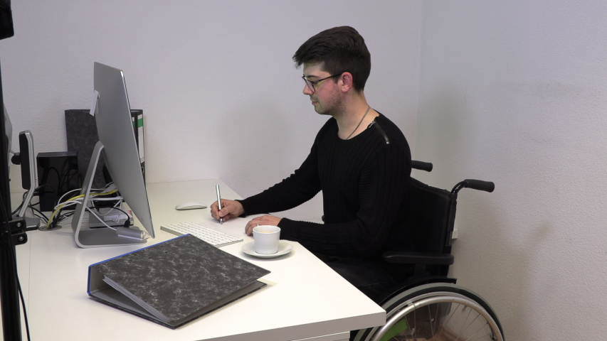 manager in the office in a wheelchair, a brunette man holds an online conference at the workplace near the computer Royalty-Free Stock Footage #1047937282