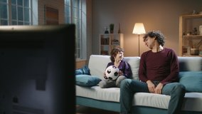 Funny asian male siblings with curly hair spending time together, watching soccer game on tv and emotionally reacting. Authentic father and son enjoying their hobby - family time concept 4k footage