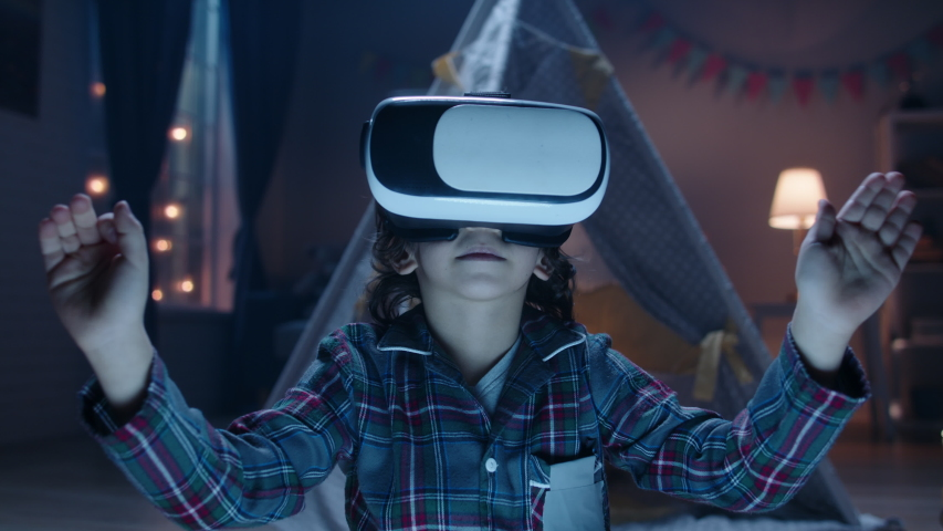 Funny little kid wearing pajamas is putting on virtual reality headset to dive into video games before bedtime , getting lit and having fun 4k footage Royalty-Free Stock Footage #1047951019
