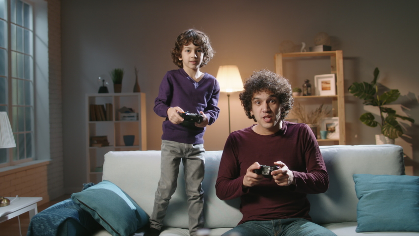 Funny south asian siblings are relaxing together, playing video games in front of tv, father and son expressing emotions while enjoying their hobby - family time concept 4k footage Royalty-Free Stock Footage #1047951034