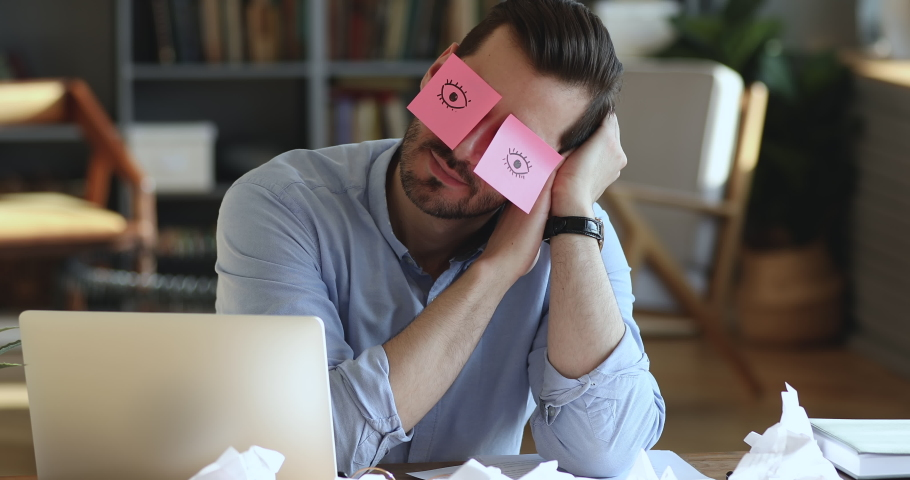 Funny lazy office worker napping at workplace covering eyes with sticky notes. Inefficient tired male employee pretends working sleeping with stickers on face sits at desk. Cheating to sleep concept Royalty-Free Stock Footage #1047963076