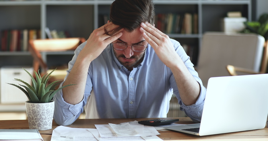 Depressed desperate man feeling worried about financial problem doing paperwork. Stressed businessman looking frustrated thinking of money debt, budget loss, bankruptcy sitting at home office desk.