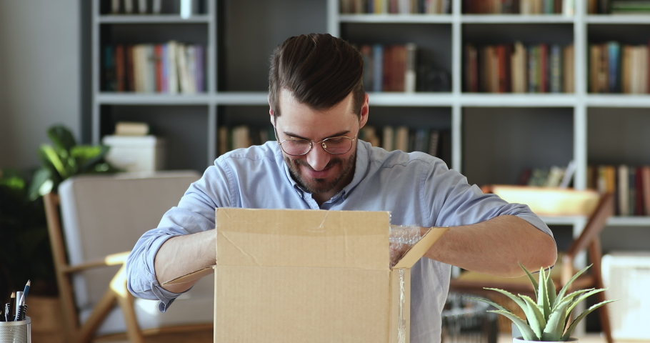 Smiling young man customer opening parcel cardboard box sitting at home office desk. Happy consumer unpacking postal shipping delivery satisfied with good purchase. Fast post shipment service concept