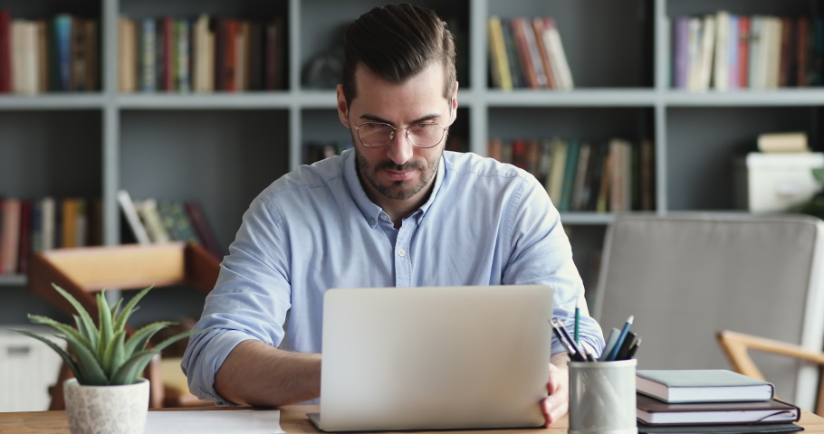 Focused business man entrepreneur typing on laptop doing research. Young male professional using computer sitting at home office desk. Busy worker freelancer working on modern tech notebook device. Royalty-Free Stock Footage #1047963103