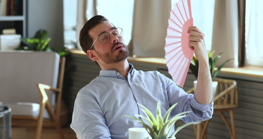 Exhausted young man waving fan suffering from summer heat inside apartment. Sweaty overheated businessman feeling hot uncomfortable frustrated about humidity, broken air conditioner in office concept. | Shutterstock HD Video #1047963109