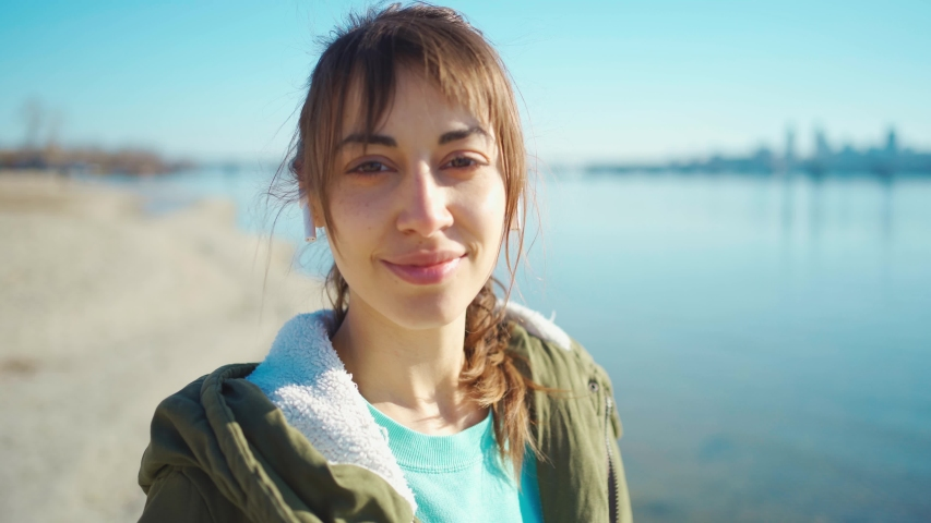 Outdoors portrait calm smiling girl in casual wear and wireless TWS Earphones enjoys by walking sandy coastline at warm sunny spring day with background of bay and cityscape   Shutterstock HD Video #1047964615