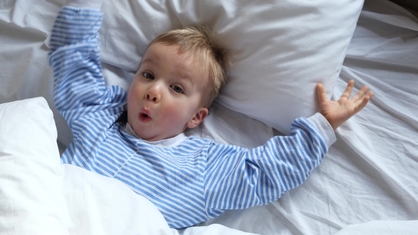 Cute funny cheerful little child boy in blue pajamas wakes up in the morning in bed, stretches and hides under the blanket again. Royalty-Free Stock Footage #1047970150