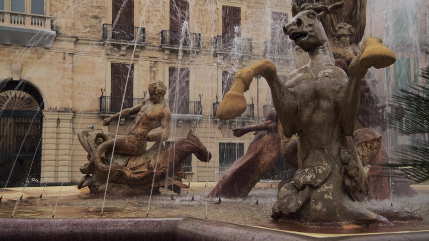 The Fountain of Diana, at the center of empty Piazza Archimede at sunrise in Ortygia island in Syracuse in Sicily, Italy