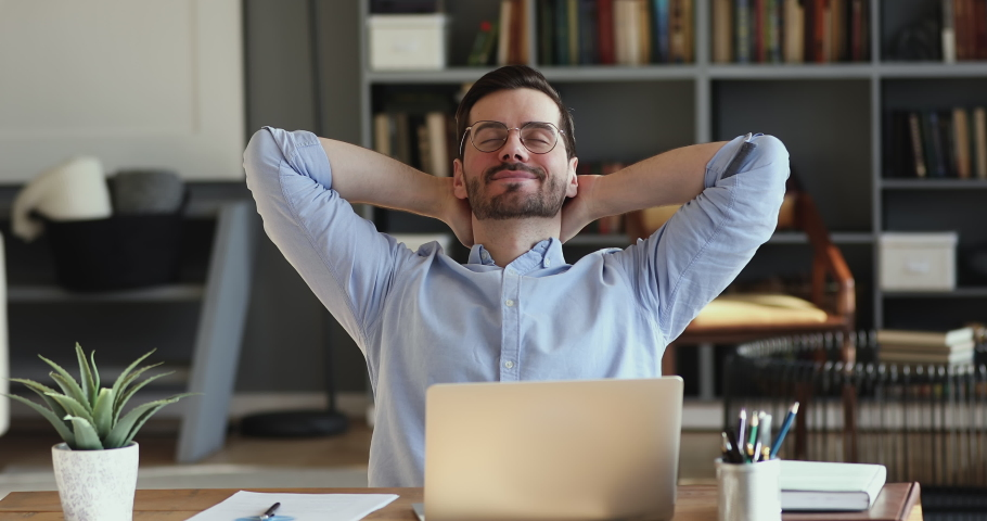 Relaxed businessman takes break to relieve stress. Satisfied happy male employee meditating sitting at workplace desk holding hands behind head. Office worker finished work feels peace of mind concept