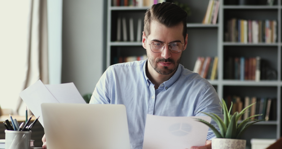 Serious young businessman checking corporate paperwork correspondence sitting at home office desk. Male entrepreneur reading documents, analyzing financial papers, preparing audit report at workplace.