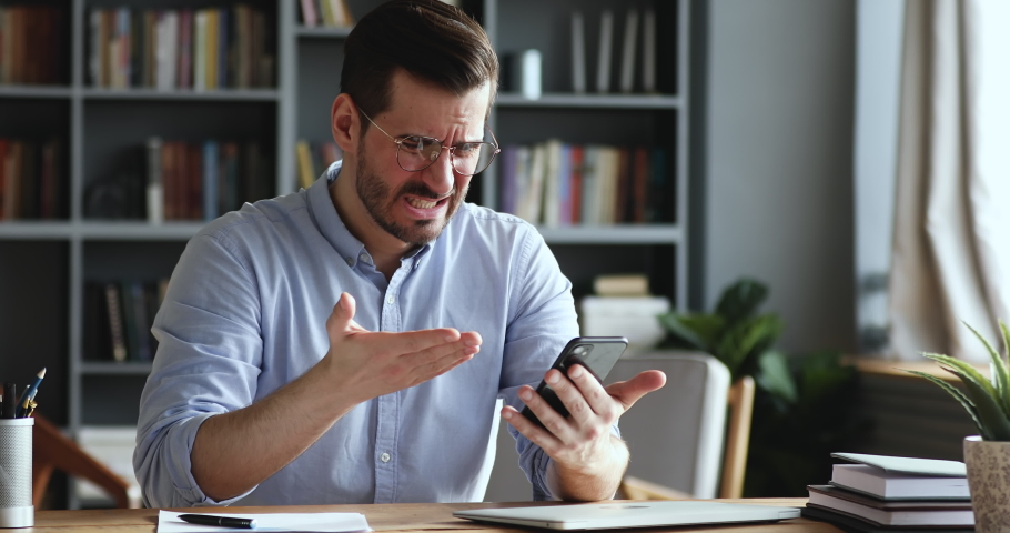Mad unhappy businessman feeling annoyed using smart phone. Angry businessman having problem with mobile spam message. Male user frustrated by low battery or bad signal concept sitting at office desk. | Shutterstock HD Video #1047988531