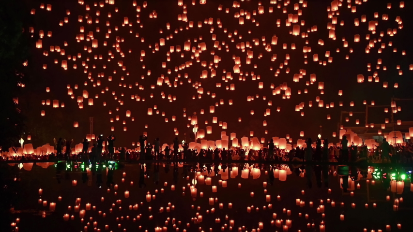 Thousands of floating fire paper lanterns in the night sky with reflection in the pool at yee peng festival. Loy Krathong celebration at Sansai, Maejo university, Chiangmai, Thailand