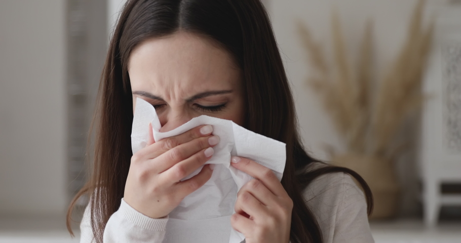 Ill allergic young woman sneezing in tissue blowing running nose. Sick girl got flu concept or caught cold, having allergy symptoms. Unhealthy lady suffer from seasonal virus disease. Close up view Royalty-Free Stock Footage #1047996661