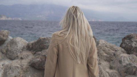A girl with blond hair in a beige coat walks along a rocky seashore