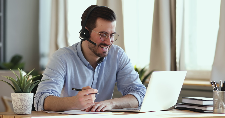 Smiling businessman wear wireless headset making conference video call on laptop. Male professional call center agent, hr manager having distance webcam chat job interview on computer in office.