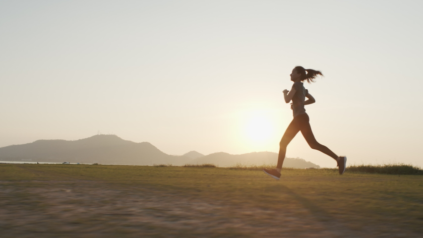 Young Asian women are exercising with outdoor running with a mountain background. When the sun sets in Thailand in summer, Concept healthy running and outdoor exercise,Tracking dolly shot