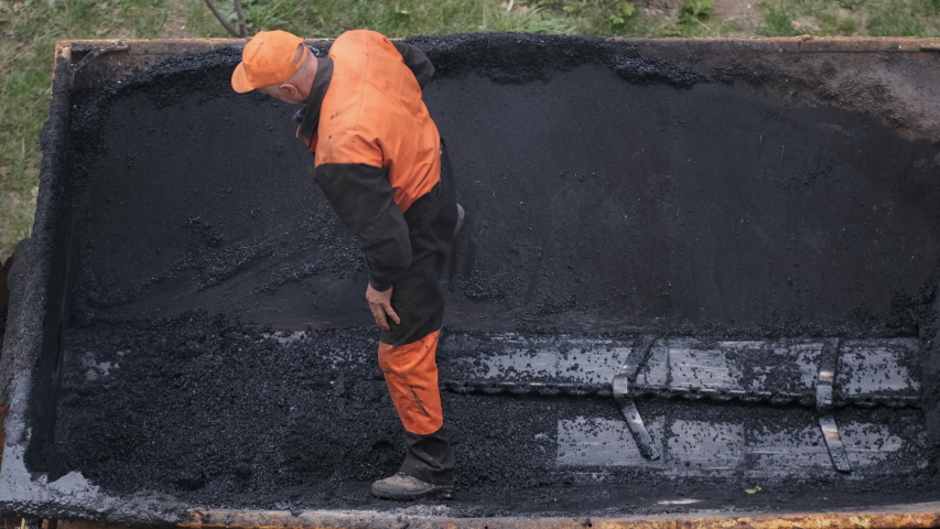 A man in a protective vest unloads asphalt from a truck with a shovel. | Shutterstock HD Video #1048033522