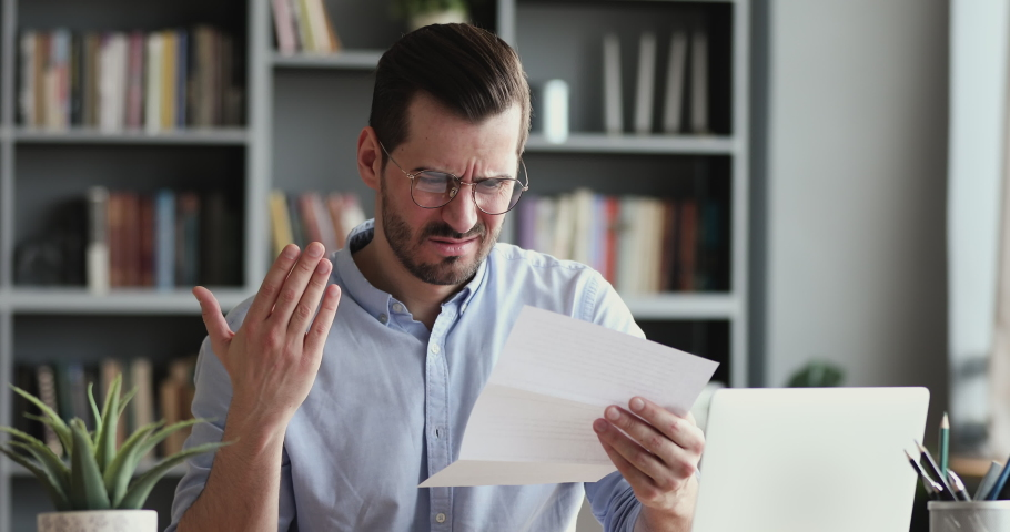 Angry stressed businessman opening envelope reading bad news in mail letter. Mad man feels frustrated about high bills, dismissal notice, bank debt, tax invoice or mistake sits at home office desk