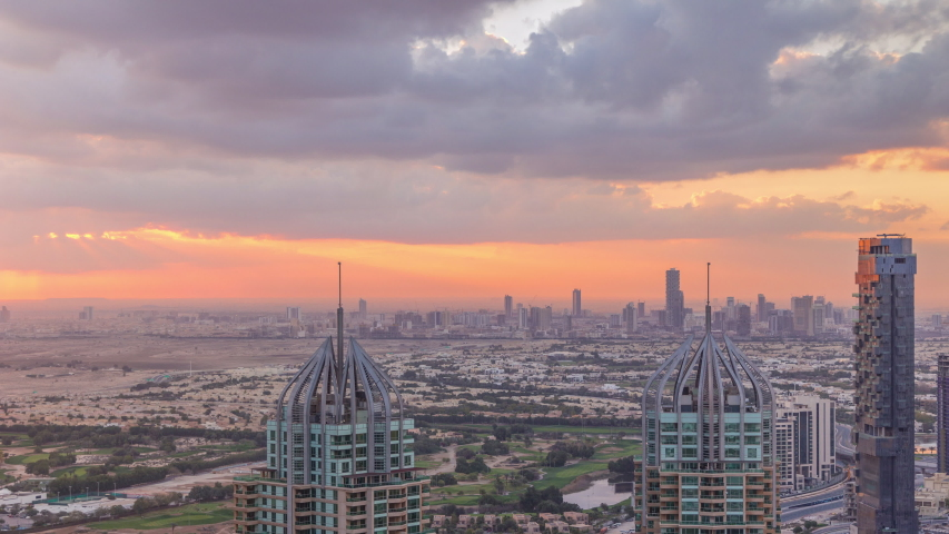 Sunrise over Dubai Marina skyscrapers and jumeirah lake towers view from the top aerial morning timelapse in the United Arab Emirates. Cloudy sky with sun beams