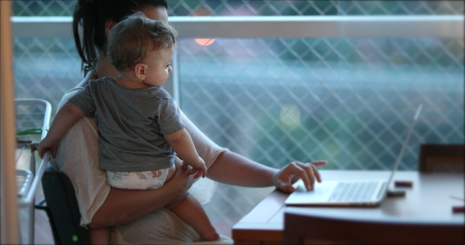 Mother multi-tasking, holding baby infant and using computer laptop at home. Candid authentic and real life mom working and parenting Royalty-Free Stock Footage #1048055704