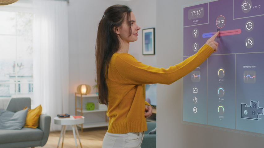 Beautiful Young Female Interacts with Augmented Reality Display. She's Changing Climate Control Setting to Higher Temperature. Smart Home Concept with Transparent Screen Made with VFX Special Effects. Royalty-Free Stock Footage #1048058680