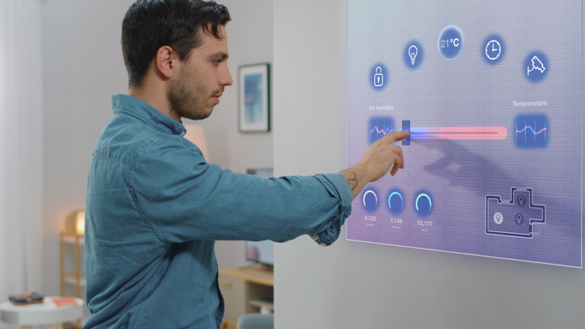 Handsome Young Man Interacts with Augmented Reality Display. He is Changing Climate Control Setting to a Higher Temperature. Smart Home Concept with Transparent Screen Made with VFX Special Effects. #1048058686