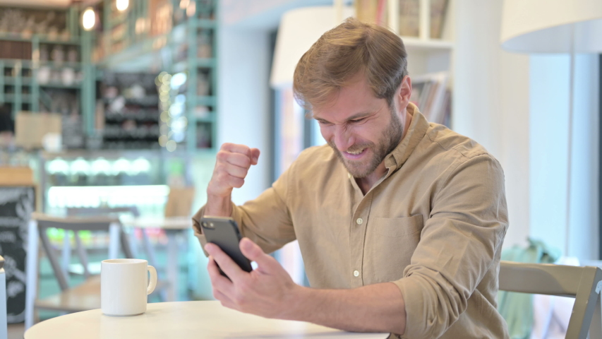 Young Man Celebrating Success on Smartphone in Cafe   Shutterstock HD Video #1048059292