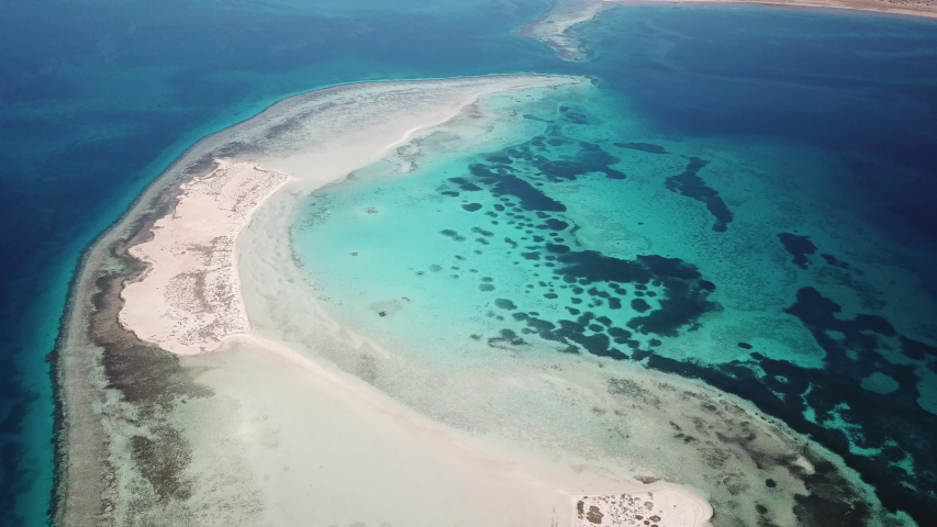 High angle drone flight of small strip of sand connecting two unspoiled islands in the Red Sea, natural landscapes and scenery in Saudi Arabia  | Shutterstock HD Video #1048061887