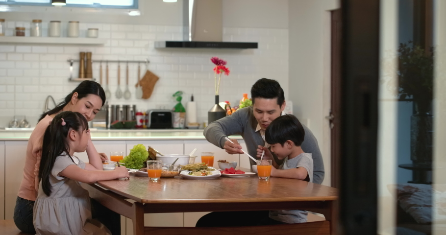 Happy family enjoy breakfast together. Cheerful young asian parents and cute small kids enjoy breakfast together on dining table at home. wonderful moment family concept 4k footage.