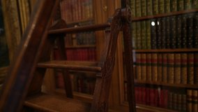 This panning up video shows old wooden library stairs and a beautiful book case.