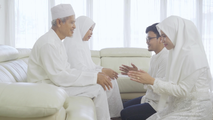 Young muslim couple apologizing to their parents during Eid Mubarak at home. Shot in 4k resolution | Shutterstock HD Video #1048101751