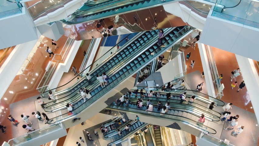 Time lapse crowded people in shopping mall. Escalators in modern shopping mall.
