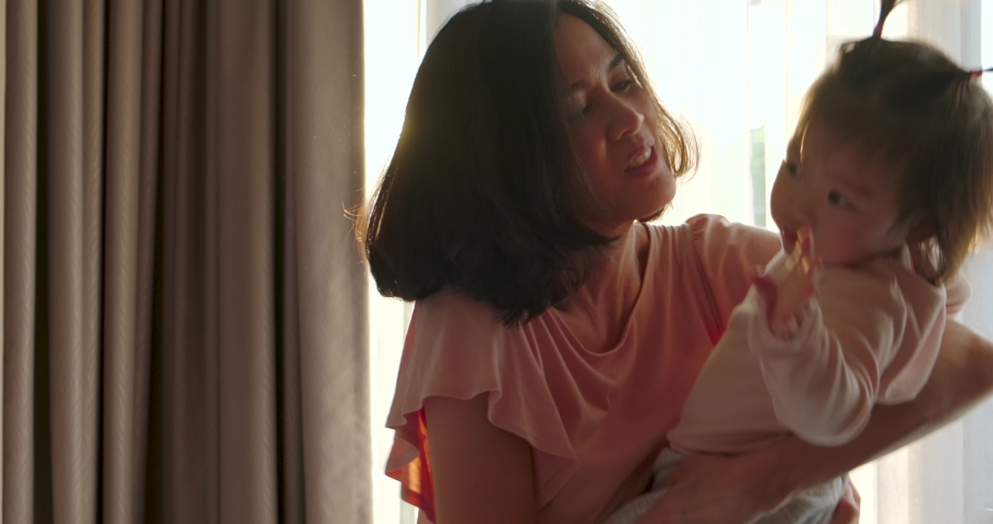 Asian beautiful mother giving warm hugs little baby girl in arms and swings around then kiss young kid in bedroom at home. Soft touch, love care, protection of mom and child in family relationship. | Shutterstock HD Video #1048109257
