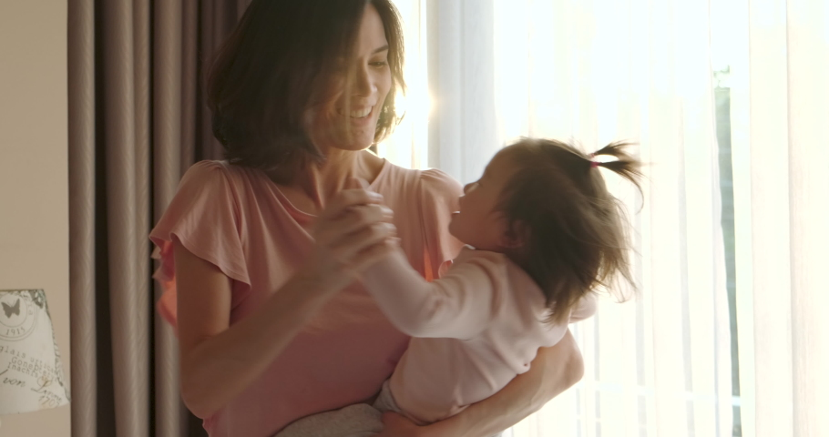 Asian beautiful mother giving warm hugs little baby girl in arms and swings around then kiss young kid in bedroom at home. Soft touch, love care, protection of mom and child in family relationship. Royalty-Free Stock Footage #1048109257