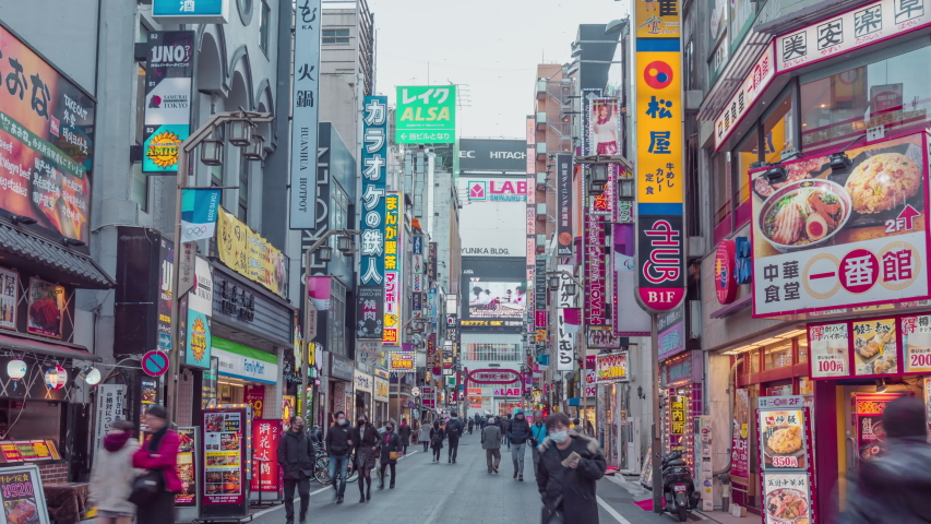 TOKYO,JAPAN 2020 February 10;Time-lapse of crowded people crossing road, car traffic at Kabukicho, entertainment night life district in Shinjuku Tokyo.Japan tourism or Asia tourist attraction concept