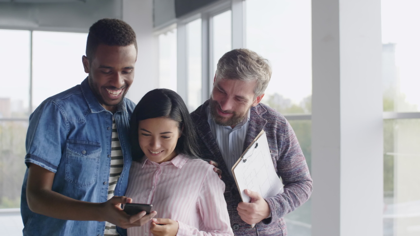 Young mixed ethnic householders holding keys from new apartments taking selfie photo with smartphone, standing with real estate agent Royalty-Free Stock Footage #1048115710