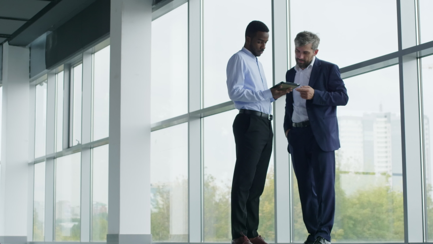 Low angle shot of two interracial financial specialists discussing calculations in tablet computer. Cityscape in background. Royalty-Free Stock Footage #1048115866