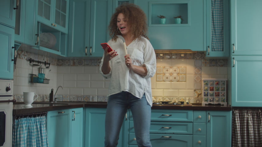 Smiling curly 20s woman in jeans dancing happily with scoop as microphone and mobile phone in hands on home blue kitchen.