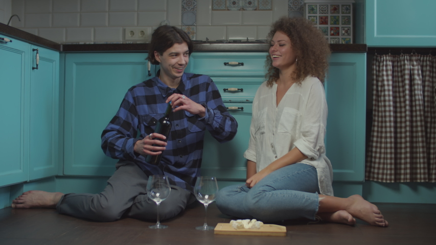 Young 20s couple drinking wine and eating cheese sitting on kitchen floor. Happy smiling man and woman celebrating with glasses of wine at home.  | Shutterstock HD Video #1048123582