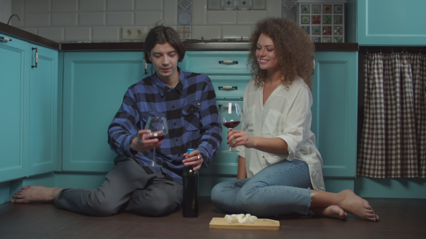 Young 20s couple drinking wine and eating cheese sitting on kitchen floor. Happy smiling man and woman celebrating with glasses of wine at home.  | Shutterstock HD Video #1048123639