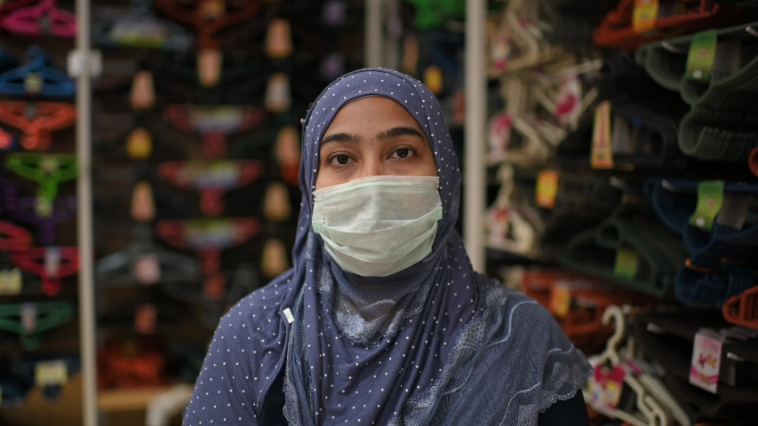 Young beautiful Muslim woman in medical mask,looking at camera.Health care and medical concept.