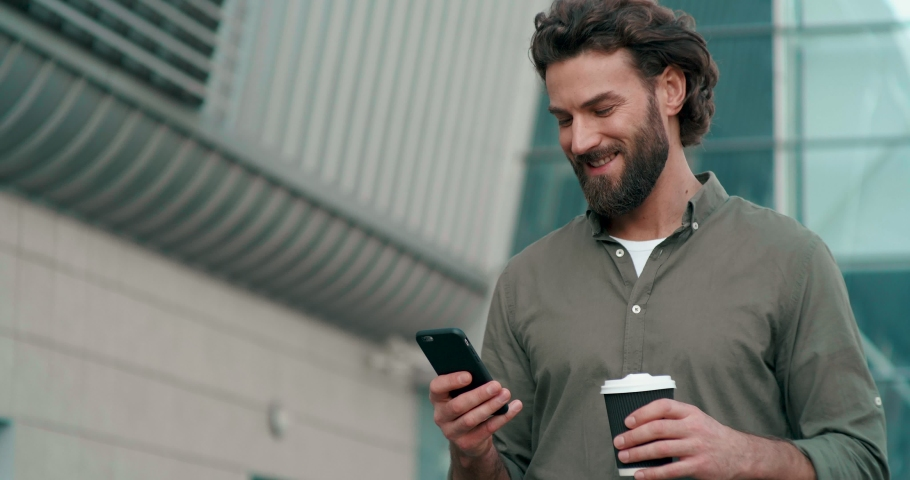 Bearded Handsome Man having a Slow walk in the Town, enjoying his Tasty Coffee. Typing Messages on his Smartphone and drinking hot Coffee. Wearing stylish clothes. Having nice Hairstyle.