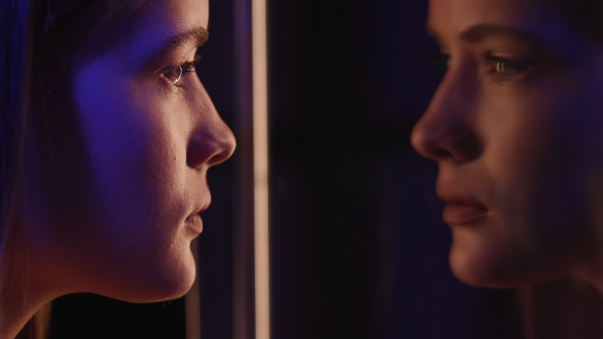 Woman Looking at Herself in Mirror Reflection. Fashion Makeup on Young Face of Girl in Multi-Colour Light of Night Club. Individuality of Charming Lady in Colourful Neon of Glass Room or Street Signs | Shutterstock HD Video #1048130191