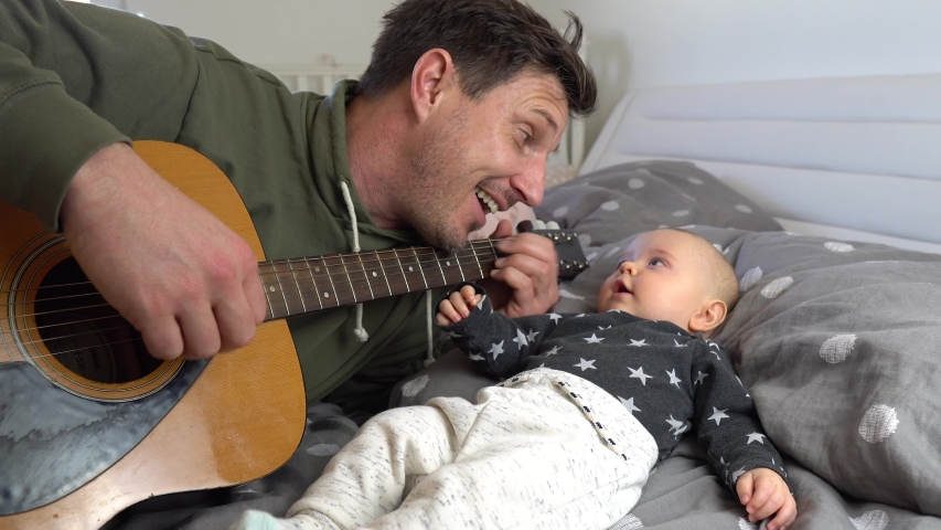 An attractive father playing guitar to his adorable baby boy on a bed. Baby listening and smiling. 4K