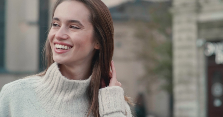 Portrait of Pretty Young Woman Standing in the City Center and Looking at Camera Objective. Wearing nice Oversized Sweater. Looking elegant and Stylish. Having brunette long Hair. | Shutterstock HD Video #1048132756