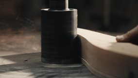 Close up video of Man's Hands working with Piece of Furniture and a Lathe in his Workshop. Carpenter scrape on the lathe a piece of Wood on his Workplace. Slow motion.